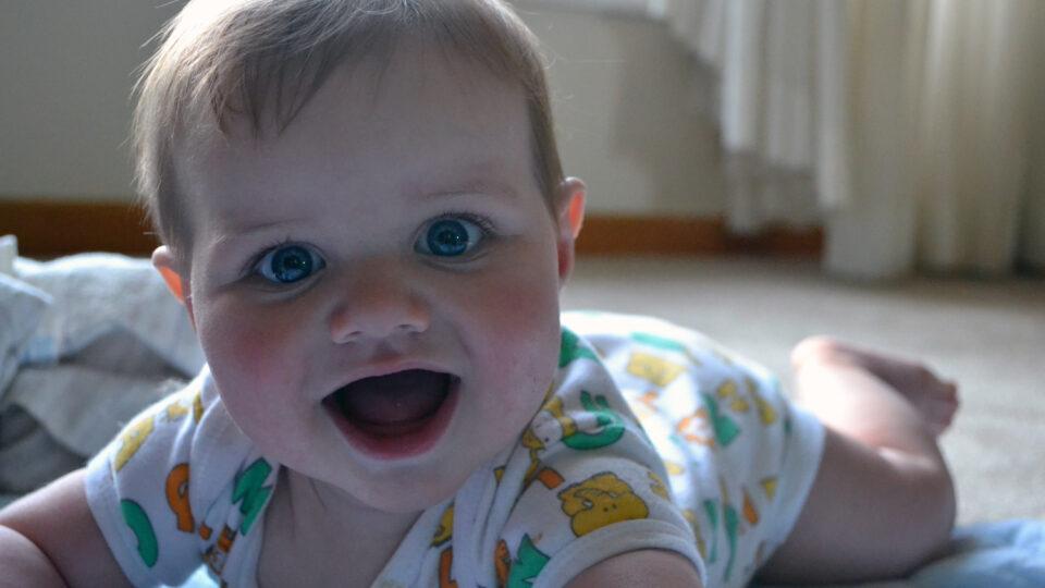 Photo - jeune bébé couché sur le sol regardant la caméra / young baby lying on floor looking at camera