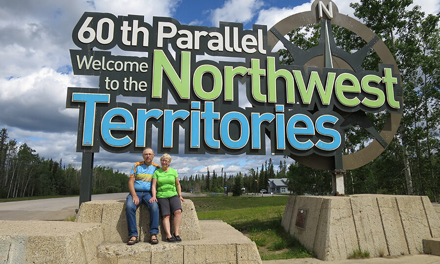 """Photo - Colleen and Norm Easson sitting in front of sign / assis devant le panneau""""60th Parallel Welcome to the Northwest Territories (en anglais)"""